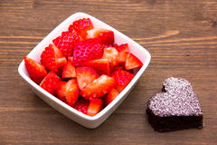 Sweet heart-shaped and strawberries on wood Royalty Free Stock Image