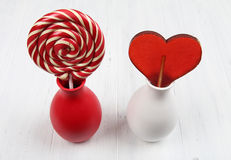 Sweet heart and spiral lollipops in vases Royalty Free Stock Photos