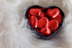 Sweet chocolate heart box. Red hert chocolates in blue heart containers on white fur. Romantic background Stock Photography
