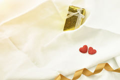 Sweet heart on valentine tosend gift box for present and tide wi. Love Valentines Day red heart and gift box and gold ribbon on off white linen fabric background Royalty Free Stock Image