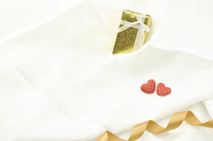 Sweet heart on valentine tosend gift box for present and tide wi. Love Valentines Day red heart and gift box and gold ribbon on off white linen fabric background Royalty Free Stock Photos