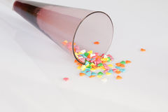 Sweet Hearts. A champagne toasting glass spilling sweet heart-shaped sprinkles Stock Photography