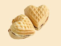 Sweet hearts. Two heart like biscuits over beige background Royalty Free Stock Images