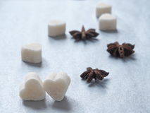 Sweet hearts and anise stars upon shiny blue background. Selective focus on the front Royalty Free Stock Photos