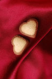 Sweet Hearts on Red Silk Background Stock Photos