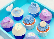 Sweet holiday buffet with vivid cupcakes. Delicious sweet buffet with cupcakes on cyan background Royalty Free Stock Image