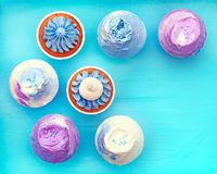 Sweet holiday buffet with vivid cupcakes. Delicious sweet buffet with cupcakes on cyan background Stock Photo