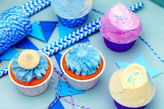 Sweet holiday decoration with vivid cupcakes. Delicious sweet buffet with cupcakes on blue background Royalty Free Stock Image
