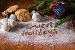 Sweet holidays with cookies and sugar. Sweet holidays is written in powdered sugar, with cookies and  sweets garnished with an ornament and evergreens Royalty Free Stock Photos