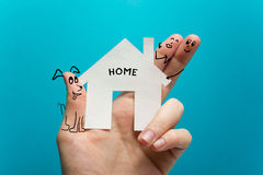 Sweet home. Hand holding white paper house figure on blue background. Real Estate Concept. Ecological building. Copy Stock Images