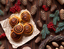 Sweet Homemade christmas baking. Cinnamon rolls buns with cocoa filling. Kanelbulle swedish dessert. Top view. Festive decoration with pine cones and Christmas Stock Image