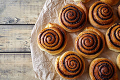 Sweet Homemade christmas baking. Cinnamon rolls buns with cocoa filling on parchment paper. Kanelbulle swedish dessert. Festive decoration with pine cones and Stock Photography