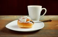 Sweet homemade cinnamon roll on the plate and cup of tea Royalty Free Stock Image