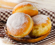 Sweet homemade Donuts with powdered sugar on a wooden plate. Royalty Free Stock Image