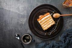 Sweet homemade honey cake. Sweet homemade layered honey cake on a black background, top view Royalty Free Stock Image