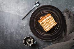 Sweet homemade honey cake. Sweet homemade layered honey cake on a black background, top view Stock Photo