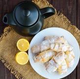 Sweet homemade lemon croissants with powdered sugar. Teapot Royalty Free Stock Image