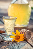 Sweet homemade liqueur with alcohol and honey. On old wooden table Stock Photo