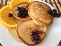 Sweet pancakes with bright orange slices and black currants berries  on a round white plate top view close up. Sweet homemade pancakes with bright orange slices Royalty Free Stock Photos