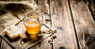 Sweet honey in the comb, glass jar with nuts. Royalty Free Stock Photo