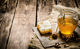 Sweet honey in the comb, glass jar with nuts. Royalty Free Stock Images