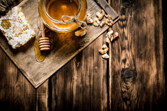 Sweet honey in the comb, glass jar with nuts. Stock Photo