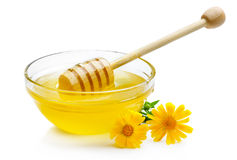 Sweet honey in glass bowl isolated with wooden dipper Royalty Free Stock Image
