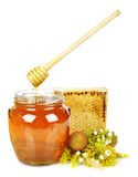 Sweet honey in glass jar. With wooden honey dripper, fresh honey in comb  and bouquet of wild flowers Stock Images