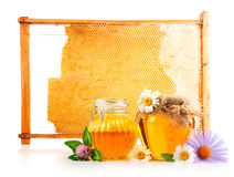 Sweet honey in glass jar with spoon and flowers Stock Photos