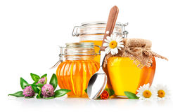 Sweet honey in glass jar with spoon and flowers Royalty Free Stock Images