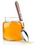 Sweet honey in glass jar with spoon and flowers Royalty Free Stock Photos