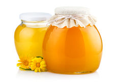 Sweet honey in glass jars with flowers isolated on white Stock Photos