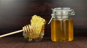 Sweet honey in a jar with honeycomb. Combs on a wooden background Royalty Free Stock Images