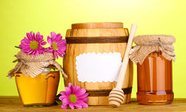 Sweet honey in jars and barrel with drizzler Royalty Free Stock Images