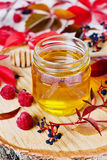 Sweet honey in pot with bow on a wooden background decorated autumn leaves and raspberry Royalty Free Stock Images