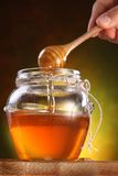 Sweet honey pouring from drizzler into the pot. Royalty Free Stock Photo