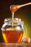 Sweet honey pouring from drizzler into the pot Royalty Free Stock Image