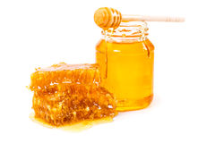 Sweet honeycomb and jar of honey with stick Royalty Free Stock Photography