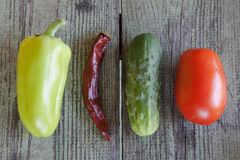 Sweet and hot peppers, cucumber and tomato on wood Stock Photos