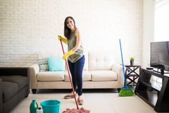 Smiling maid cleaning house with mop. Sweet housewife loving cleanliness is sweeping floor using mop and floor cleaner in living area Royalty Free Stock Image