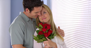Sweet husband surprises his wife with flowers Stock Images
