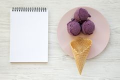Sweet ice cream cone with ice cream scoops on a pink plate, blank notepad over white wooden background, top view. royalty free stock photos