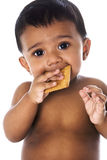 Sweet Indian baby eating a cookie Stock Photos