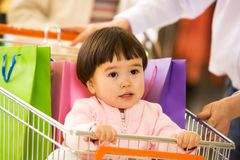 Sweet infant. Photo of cute little girl looking upwards while sitting in handcart in the mall Stock Photos