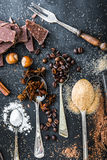 Sweet ingredients and chocolate on a table. Sweet powdered ingredients in a spoon and chocolate on a table black stock photography