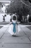 Sweet Innocence in Blue. Young girl skips down the path at a garden.  She is dressed in white with a blue bow.  Black and white photo with blue colorized bow Stock Photography