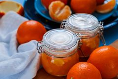 Sweet jam from oranges in small jars with fresh oranges. Sweet jam from oranges in small jars with fresh oranges on the blue table Royalty Free Stock Photography