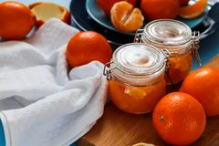 Sweet jam from oranges in small jars with fresh oranges. Sweet jam from oranges in small jars with fresh oranges on the blue table Stock Image