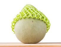 Sweet Japanese melon in green net foam protection place on woode Stock Photo