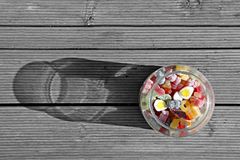 Sweet jar abstract. Aerial view abstract photo of a glass sweet jar full of kiddies favourite sweets and jellies on wood decking background with sun creating Royalty Free Stock Images